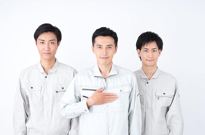 灰色の作業着の男性3人正面