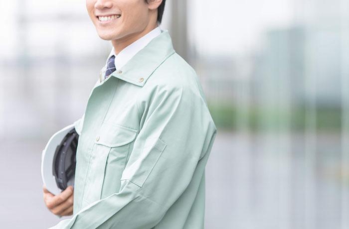 浅葱色の作業着の人物